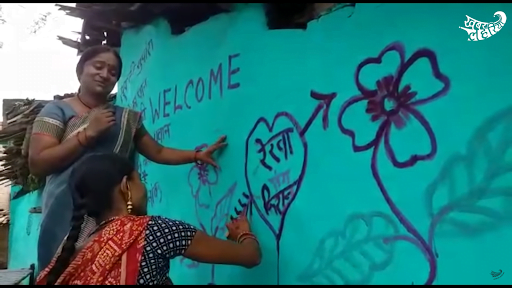 A woman paints a heart welcoming the newlywed couple Rekha and Kishan to their new life on the eve of their wedding in Banda, 2019.